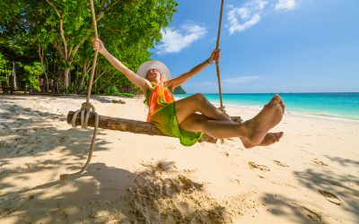 Happy and attractive woman with colorful sarongs and white wide-brimmed hat swinging on tropical white beach of Koh Rok Islands, Ko Lanta, Thailand paradise for snorkelers and divers.