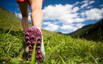 Woman walking in mountains in sport hiking shoes. Jogging trekking or training outside in summer nature inspiring motivational health and fitness concept.